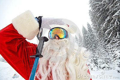 Santa Claus skiing in the mountains on snow in winter in Christm