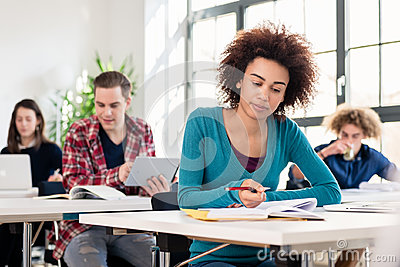 Student concentrating while writing an essay during class in an