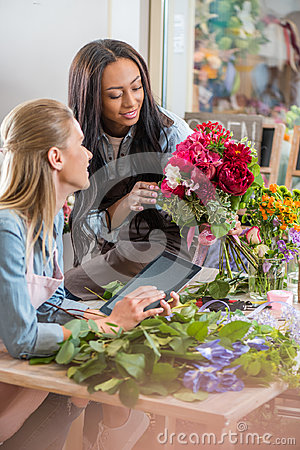 Young multiethnic florists working with digital tablet and flowers in flower shop