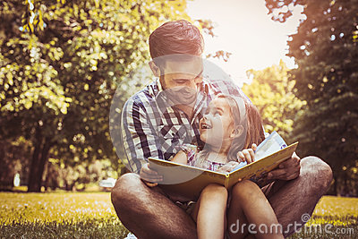 Single father sitting on grass with little daughter.