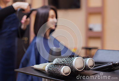 The hairdresser dries her hair a brunette girl in a beauty salon.