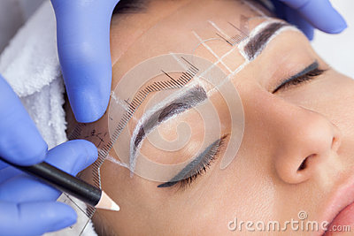 Permanent make-up for eyebrows of beautiful woman with thick brows in beauty salon