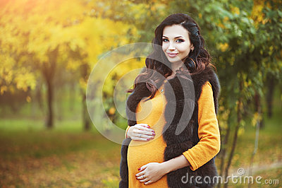 Beautiful young happy pregnant woman staying in fashion clothes in autumn park touching her belly and smiling.