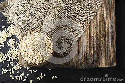 Pearl dry cereal in a vintage wooden bowl on a plain dark background for text placement and advertising. Selective focus