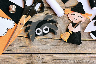 Quick Halloween crafts. Felt witch doll, spider decorations on a vintage wooden background. Needlework tools and materials