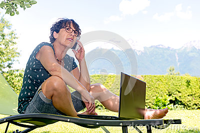 Woman sitting on the deck chair in garden using smartphone