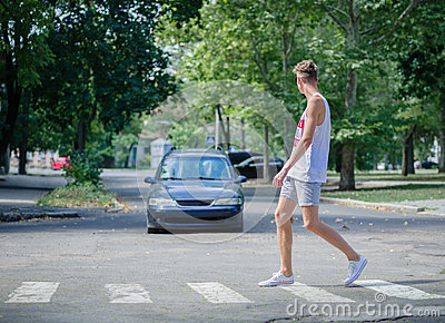 Man walking in front of a car. A boy crossing street on a blurred background. Careful on the road concept. Copy space.