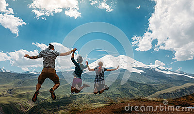 stock image of three friend jumping holding hands mountains elbrus landscape on background. lifestyle travel happy emotions success concept summe