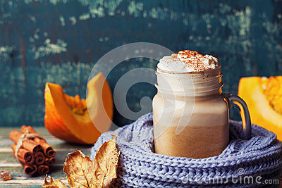 Flavored pumpkin spiced latte or coffee in cup decorated knitted scarf on teal vintage background. Autumn, fall, winter hot drink.