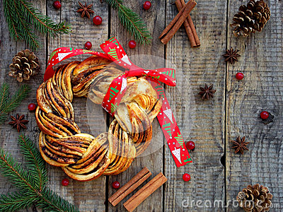 Cinnamon cocoa brown sugar wreath buns. Sweet Homemade christmas baking. Roll bread, spices, decoration on wooden background. New