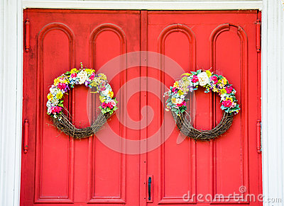 Weathered bright red church door with flower wreaths