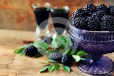 Blackberry fruit liqueur in two shot glasses with berries and gr