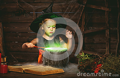 Halloween. little witch child cooking potion in cauldron with