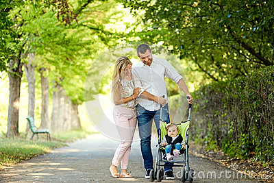 Mother, father and baby in a stroller walking in the park.