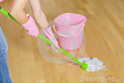 Woman in protective gloves using a wet-mop while cleaning floor