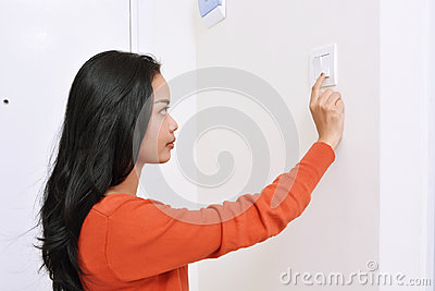 Beautiful asian woman turning off the light with wall switch