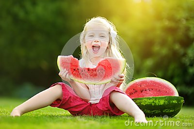 Funny little girl biting a slice of watermelon outdoors on warm and sunny summer day