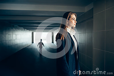 Beautiful lonely woman in subway tunnel with frighten silhouette