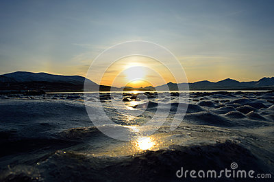 Golden sunrise over blue fjord and snowy mountain with reflection on thick ice