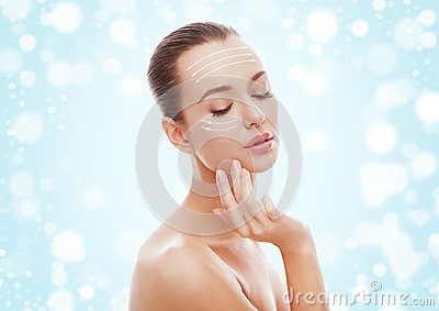 stock image of beautiful young girl touching her face on blue background and snow. plastic surgery, facelift and rejuvenation concept.