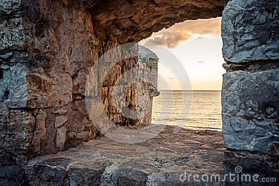 Old ruins background with scenic sunset over sea through ancient castle window with dramatic sky and perspective view with effect