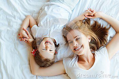 Happy family mother and child daughter laugh in bed