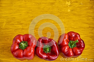 Three red bell pepper close up on wooden yellow background with copy space. Bell peppers on wooden yellow texture close up