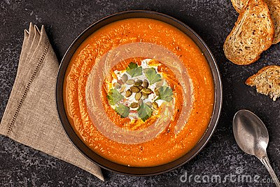 Pumpkin and carrot soup with cream, seeds and parsley.