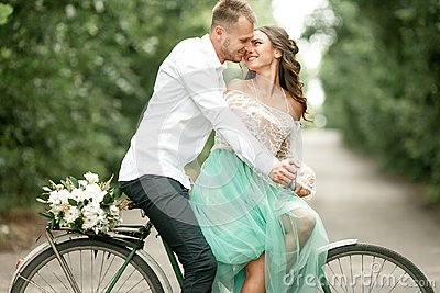 Bride and groom sit on bicycle on forest road, embrace and smile