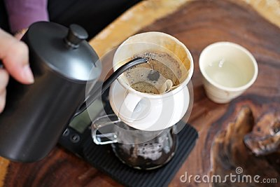 Barista pouring hot water over coffee grounds making  drip brew coffee.