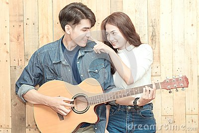 stock image of couple playing acoustic guitar