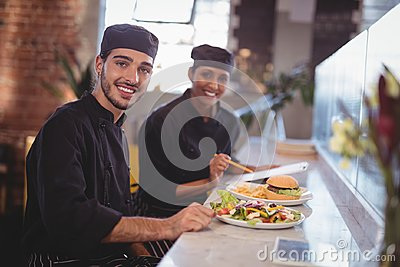 Portrait of smiling young wait staff sitting with food and clipboard at counter