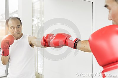 Portrait of Asian senior fighter man punching with red boxing gl