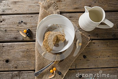 Granola bar and milk on wooden table