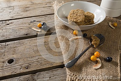 Granola bar and berry fruit on wooden table