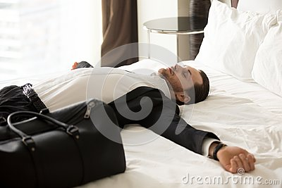 Exhausted businessman laying on bed in hotel room.