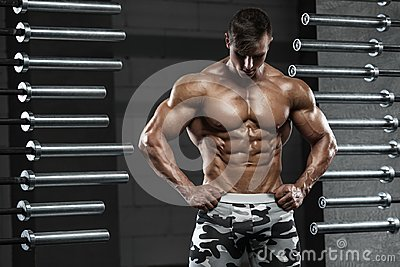 Muscular man showing muscles, posing in gym. Strong male naked torso abs, working out