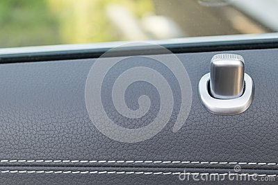 Door handle with lock control buttons of a luxury passenger car. Black leather interior of the luxury modern car. Modern car