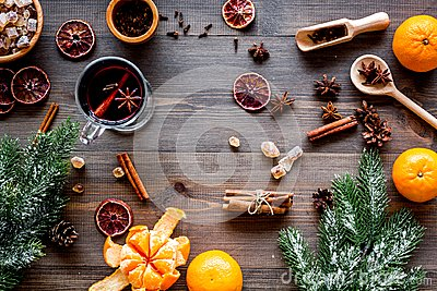 Merry christmas in winter evening with warm drink. Hot mulled wine or grog with fruits and spices on wooden background