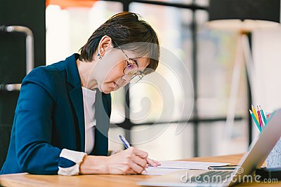 Middle age Asian woman working on paperwork in modern office, with laptop computer. Business owner or entrepreneur concept