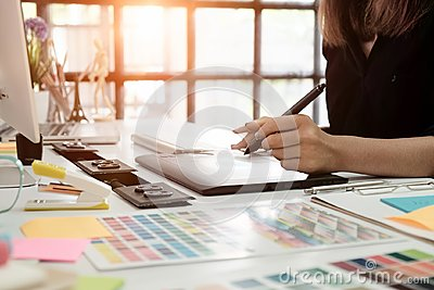 stock image of graphic design desk hand using mouse pan sketch device on creative desk.
