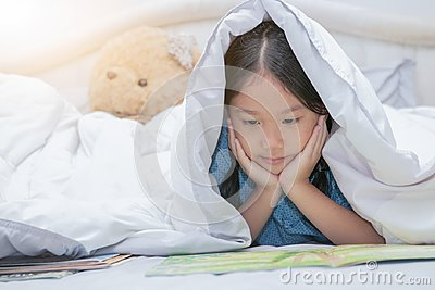 Cute little asian girl reading fairy tales book under blanket on