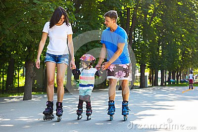Cute baby boy and his mom learning inline skating