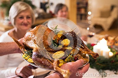 Family celebrating Christmas. Roasted turkey on tray.
