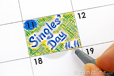 Woman fingers with pen writing reminder Singles Day 11.11 in cal