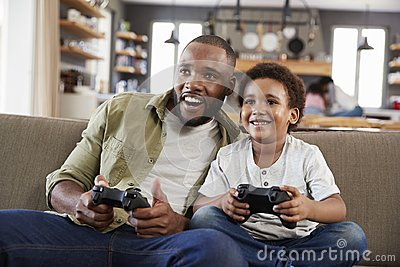 Father And Son Sitting On Sofa In Lounge Playing Video Game