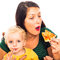 Woman eating pizza and child drinking