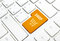Shop business concept. Orange shopping cart button or key on white keyboard