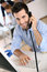 Happy businessman talking on phone in office