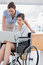 Disabled businesswoman looking at laptop with her colleague